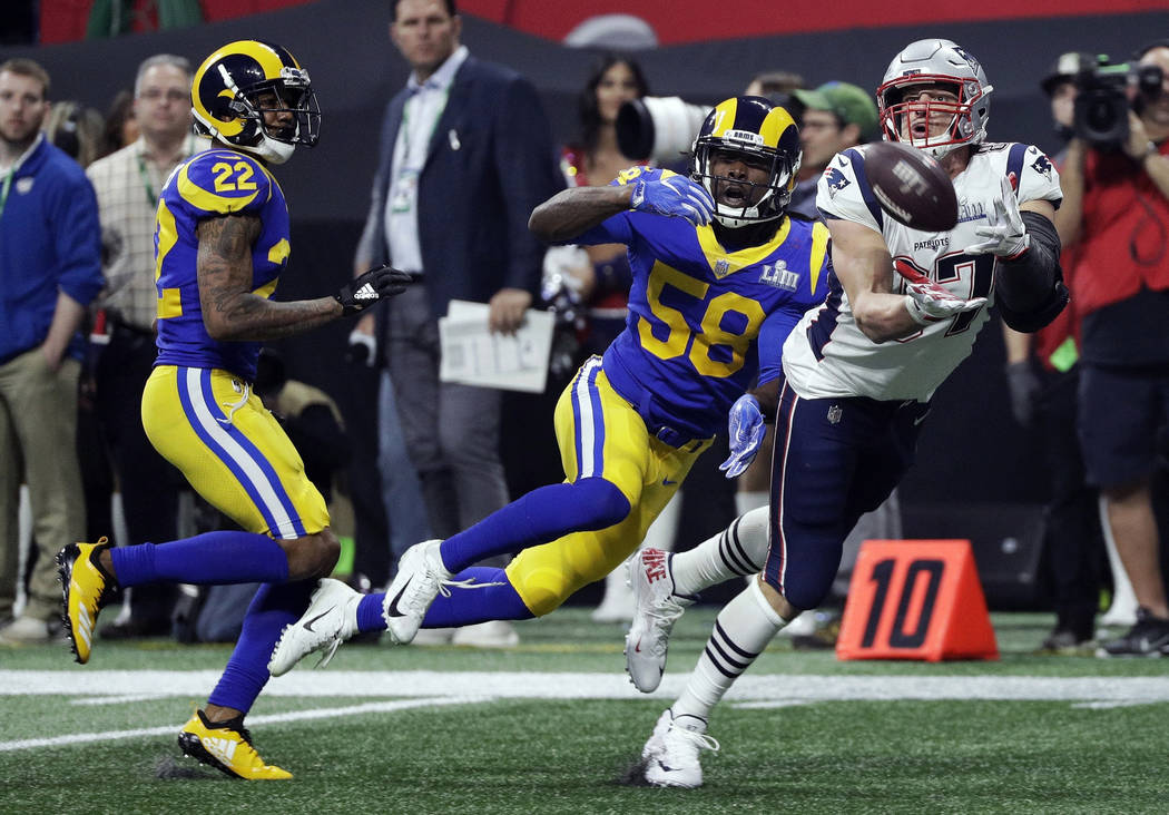 New England Patriots' Rob Gronkowski (87) catches a pass in front of Los Angeles Rams' Marcus Peters (22) and Cory Littleton (58) during the second half of the NFL Super Bowl 53 football game Sund ...