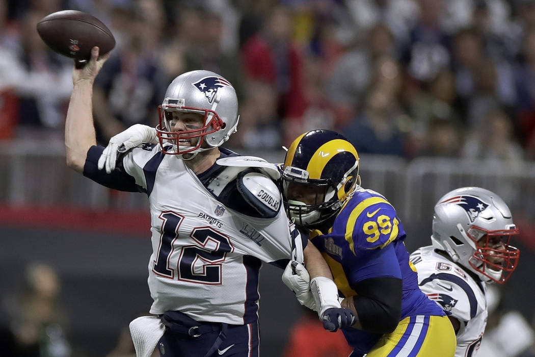 New England Patriots' Tom Brady (12) passes under pressure form Los Angeles Rams' Aaron Donald (99) during the first half of the NFL Super Bowl 53 football game Sunday, Feb. 3, 2019, in Atlanta. ( ...