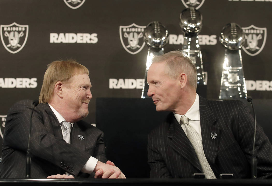 Mike Mayock, right, shakes hands with Oakland Raiders owner Mark Davis at a news conference announcing Mayock as the team's general manager in Oakland, Calif., Monday, Dec. 31, 2018. (AP Photo/Jef ...