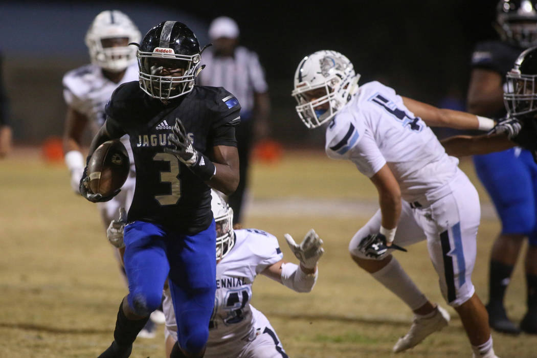 Desert Pines High School's Jamel Brown (3) runs with the ball after dodging a tackle from Centennial High School's Jacob Buchanan (23) during the first half of a varsity playoff football game at D ...