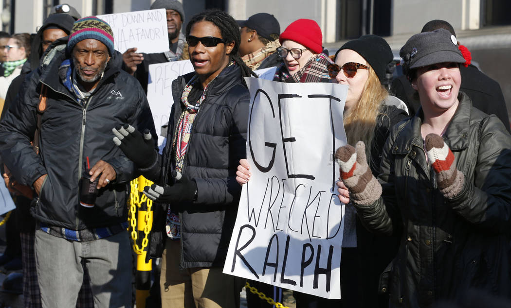 Demonstrators hold signs and chant outside the Governors office at the Capitol in Richmond, Va., Saturday, Feb. 2, 2019. The demonstrators are calling for the resignation of Virginia Governor Ralp ...