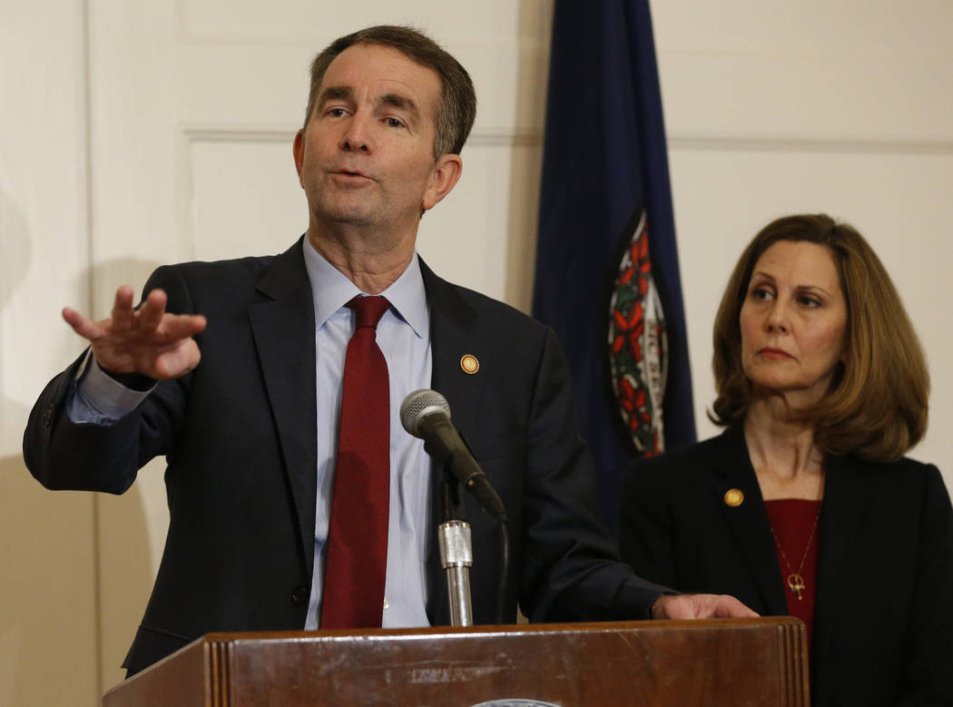 Virginia Gov. Ralph Northam, left, gestures as his wife, Pam, listens during a news conference in the Governors Mansion at the Capitol in Richmond, Va., Saturday, Feb. 2, 2019. Northam is under fi ...