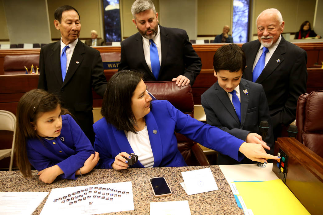 Assemblywoman Rochelle Nguyen, D-Las Vegas, bottom center, shows her children Hannah Lay, 6, and Henry Lay, 8, how she will vote in the Legislative Building in Carson City on the first day of the ...
