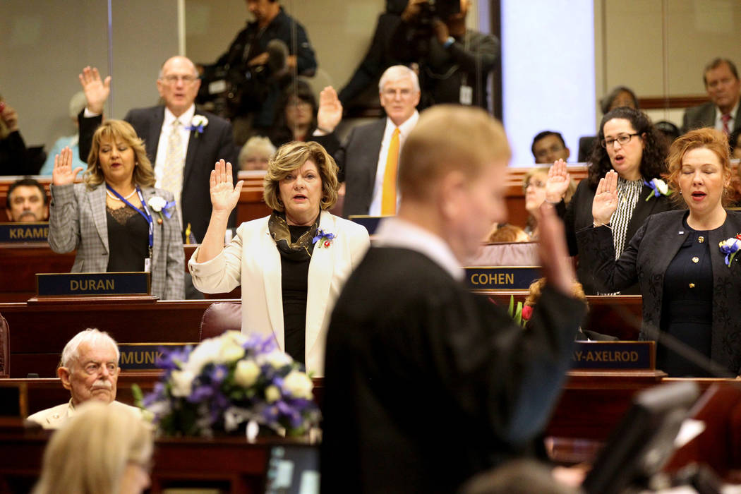 Supreme Court Chief Justice Mark Gibbons swears in members of the Assembly in the Legislative Building in Carson City on the first day of the 80th session of the Nevada Legislature Monday, Feb. 4, ...
