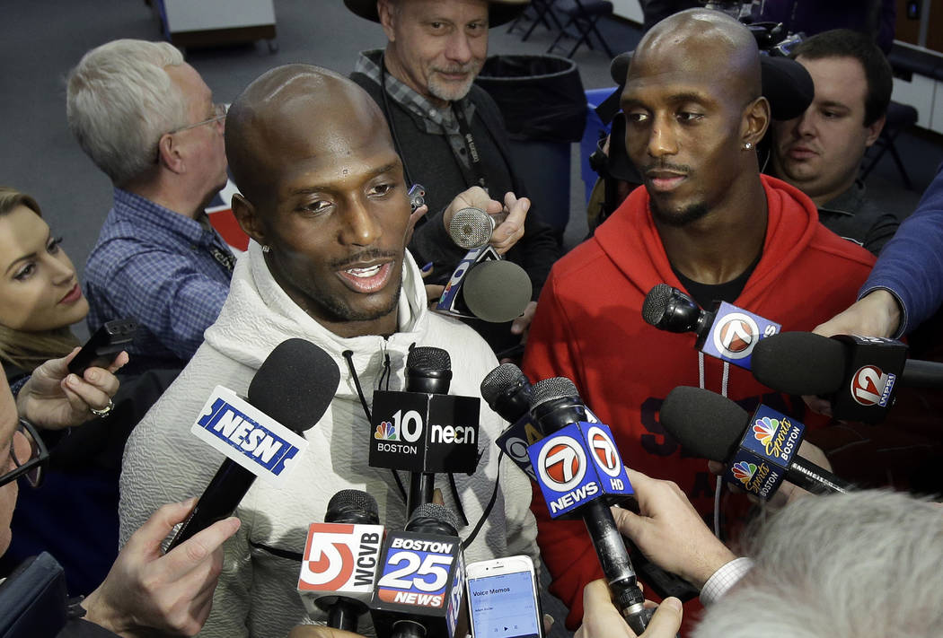 New England Patriots cornerback Jason McCourty, left, and his brother free safety Devin McCourty, right, faces reporters in the team's locker room following their arrival at Gillette Stadium, Mond ...