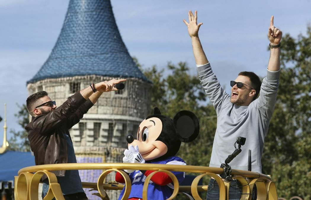 Super Bowl MVP Julian Edelman and Patriots quarterback Tom Brady, right, celebrate with Mickey Mouse in the Super Bowl victory parade in the Magic Kingdom, at Walt Disney World, in Lake Buena Vist ...