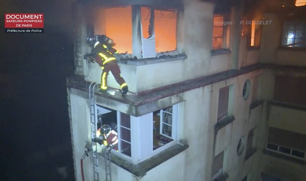 In this image taken from video released by the Paris Fire Dept., firemen scale the top floors of an apartment building on fire, Tuesday, Feb. 5, 2019, in Paris, France. A fire in a Paris apartment ...
