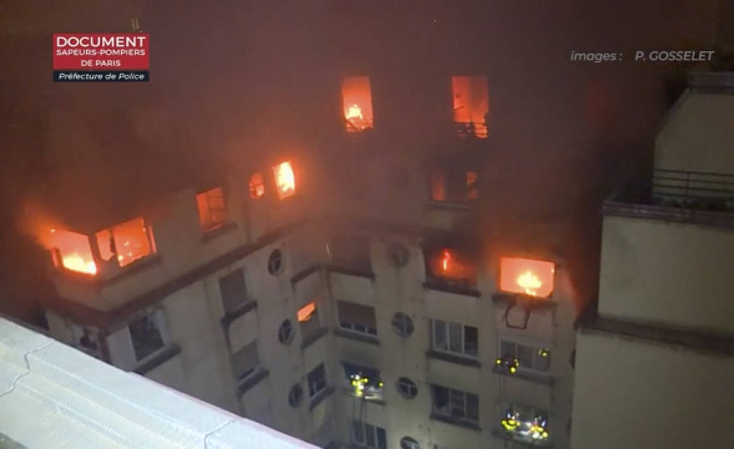 In this image taken from video released by the Paris Fire Dept., a fire rages through the top floors of an apartment building, Tuesday, Feb. 5, 2019, in Paris, France. A fire in a Paris apartment ...