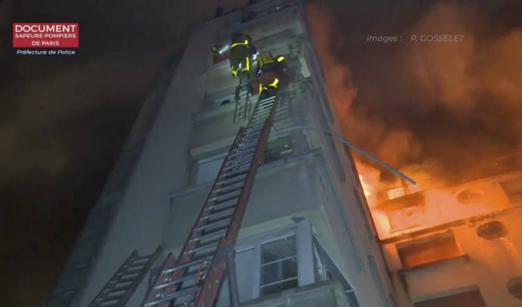 In this image taken from video released by the Paris Fire Dept., firemen climb ladders to the top floors of an apartment building on fire, Tuesday, Feb. 5, 2019, in Paris, France. A fire in a Pari ...