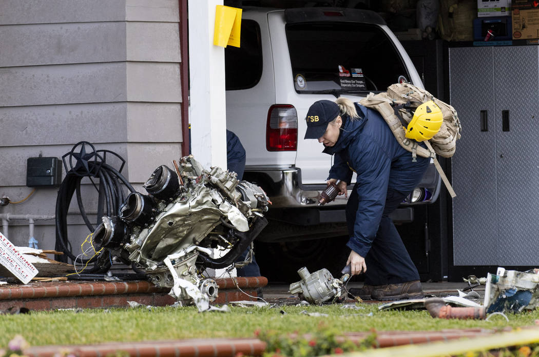 A National Transportation Safety Board worker takes a photo of an engine that came to rest against a house on Crestknoll Dr. in Yorba Linda, Calif on Monday, February 4, 2019. The debris field fro ...