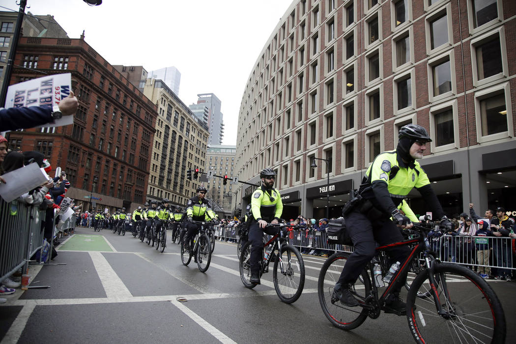 Police roll by on bikes as fans gather near Boston City Hall, Tuesday, Feb. 5, 2019, to watch the New England Patriots football team victory parade through the streets of Boston. The Patriots are ...
