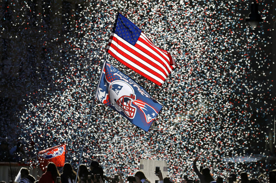 Confetti flies as fans watch the New England Patriots parade through downtown Boston, Tuesday, Feb. 5, 2019, to celebrate their win over the Los Angeles Rams in Sunday's NFL Super Bowl 53 football ...