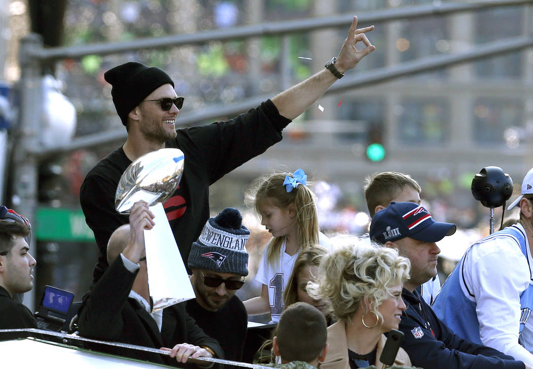 New England Patriots' Tom Brady rides beside the trophy as the team parades through downtown Boston, Tuesday, Feb. 5, 2019, to celebrate their win over the Los Angeles Rams in Sunday's NFL Super B ...