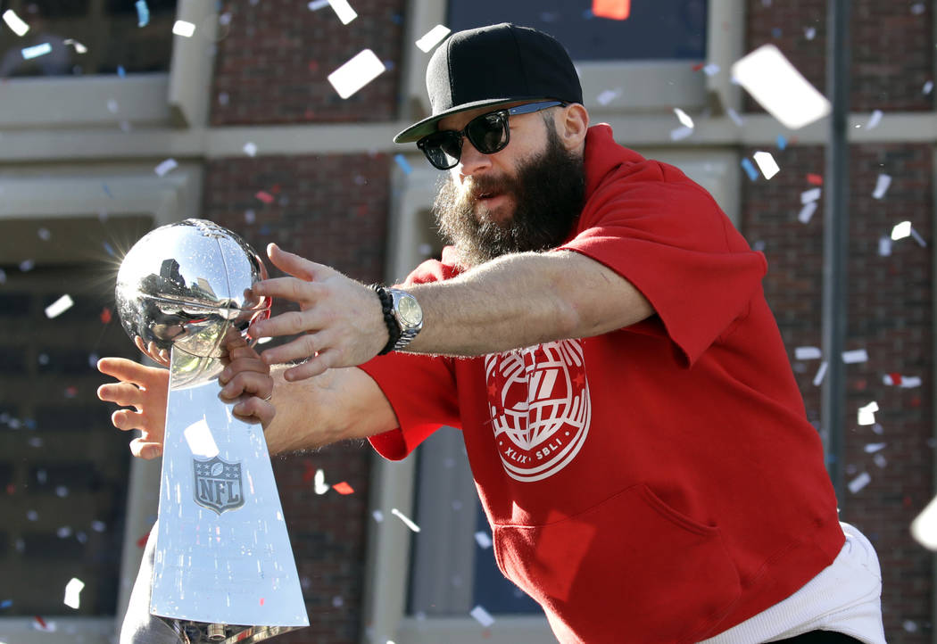 New England Patriots' Julian Edelman reaches for a Super Bowl trophy during their victory parade through downtown Boston, Tuesday, Feb. 5, 2019, to celebrate their win over the Los Angeles Rams in ...