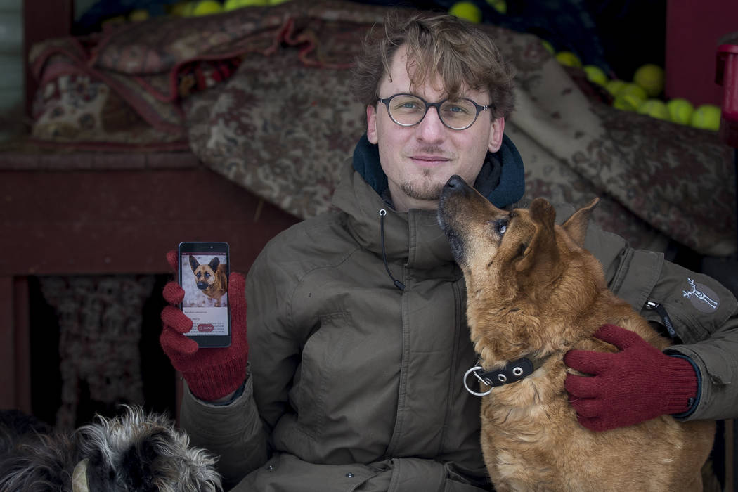 Vaidas Gecevicius, who developed an app helping to match stray dogs with potential owners, poses for a picture with a dog and shows this dog's profile on the app in Vilnius, Lithuania on Saturday, ...