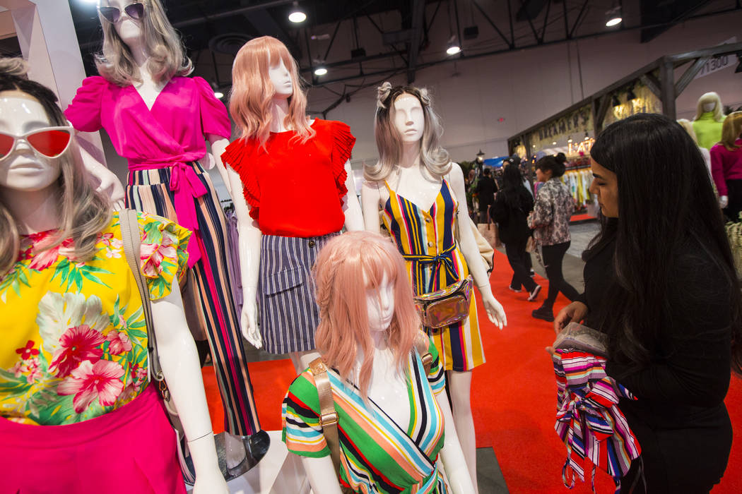 Renata Hernandez, right, styles mannequins at the Lulumari and Milk and Honey Booth during WWDMAGIC, part of the MAGIC trade show, at the Las Vegas Convention Center in Las Vegas on Tuesday, Feb. ...