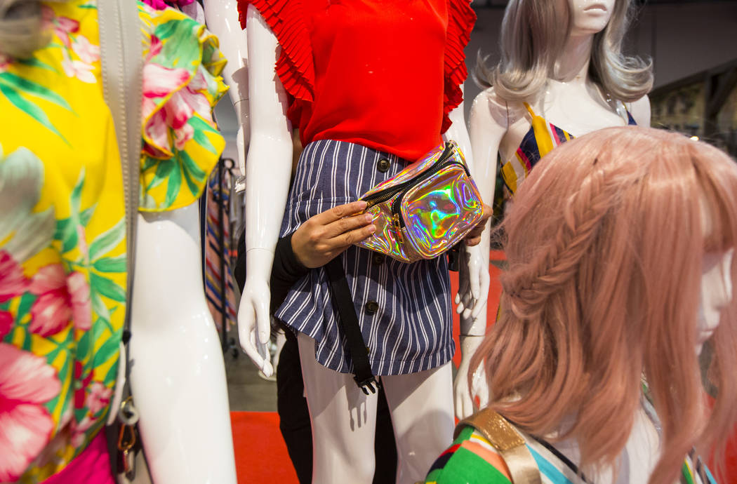 Renata Hernandez styles mannequins at the Lulumari and Milk and Honey Booth during WWDMAGIC, part of the MAGIC trade show, at the Las Vegas Convention Center in Las Vegas on Tuesday, Feb. 5, 2019. ...