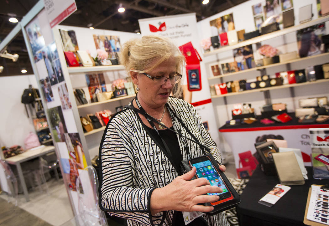 Tami Lange, CEO of Save the Girls, talks about touch screen purse products during WWDMAGIC, part of the MAGIC trade show, at the Las Vegas Convention Center in Las Vegas on Tuesday, Feb. 5, 2019. ...