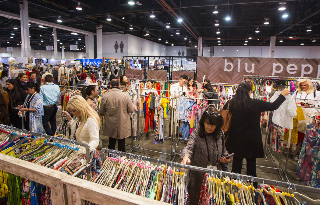 Tammy Matthews of Ohio, right, browses clothing at Blu Pepper during WWDMAGIC, part of the MAGIC trade show, at the Las Vegas Convention Center in Las Vegas on Tuesday, Feb. 5, 2019. (Chase Steven ...