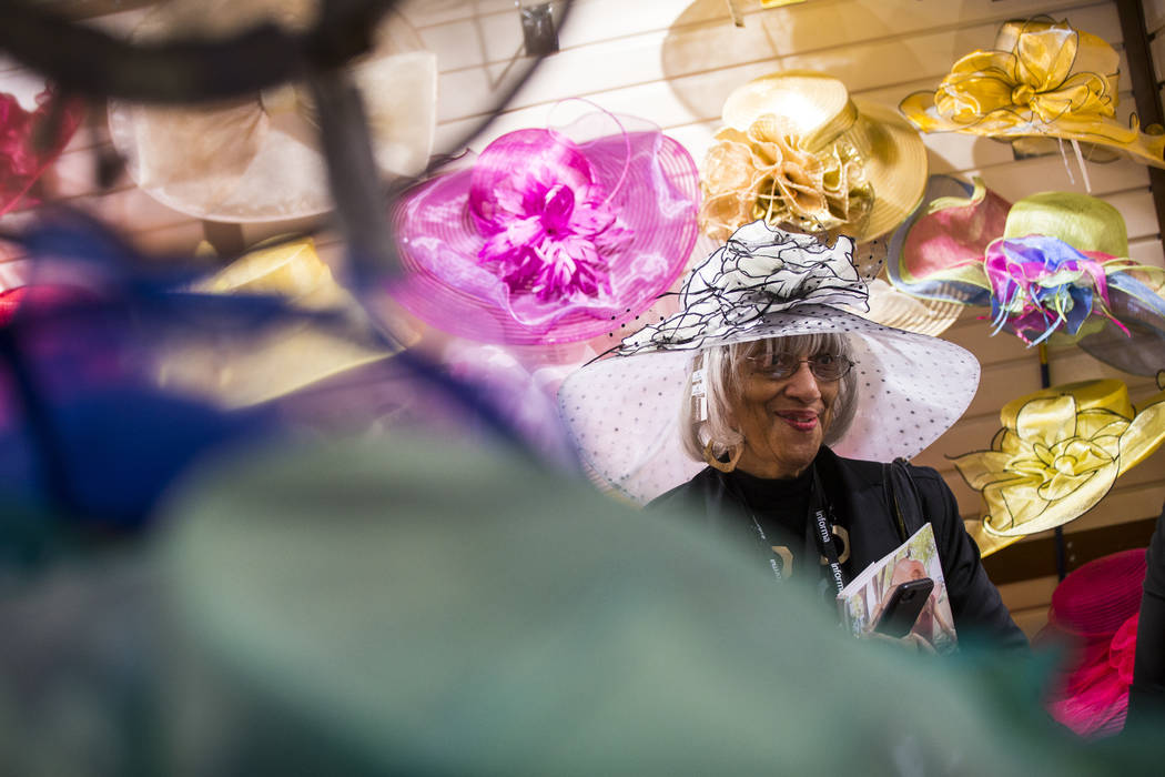 Elva Wallace, of Fair Oaks, Calif., smiles at her husband while trying on a hat by Something Special Hats during WWDMAGIC, part of the MAGIC trade show, at the Las Vegas Convention Center in Las V ...
