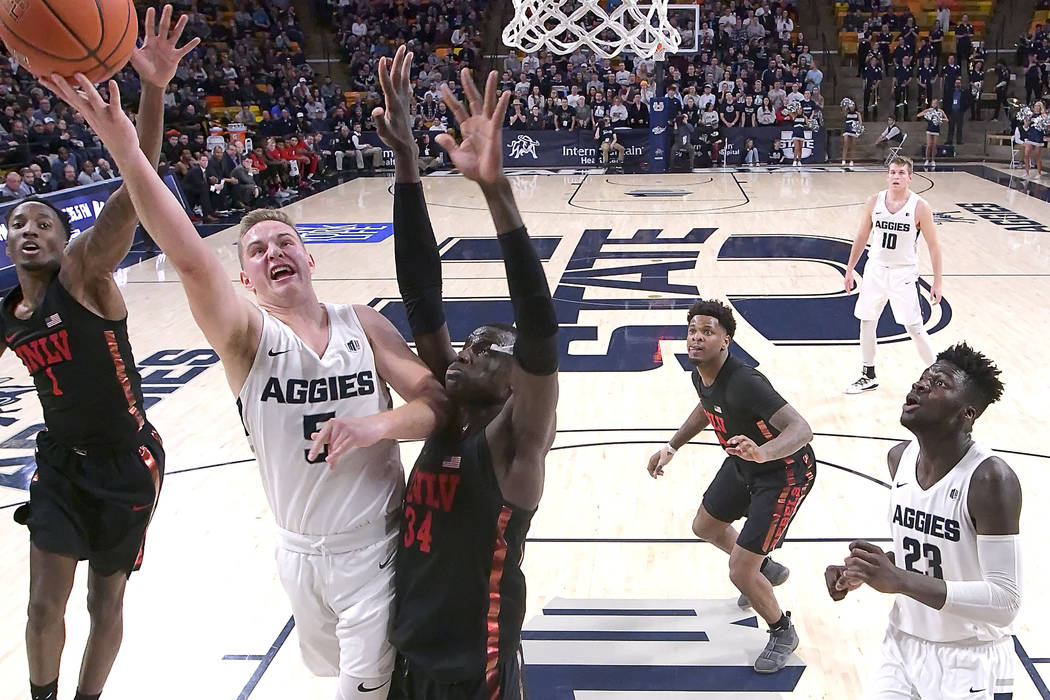 Utah State guard Sam Merrill (5) shoots as UNLV guard Kris Clyburn (1) and forward Cheikh Mbacke Diong (34) defend during an NCAA college basketball game Saturday, Feb. 2, 2019, in Logan, Utah. (E ...