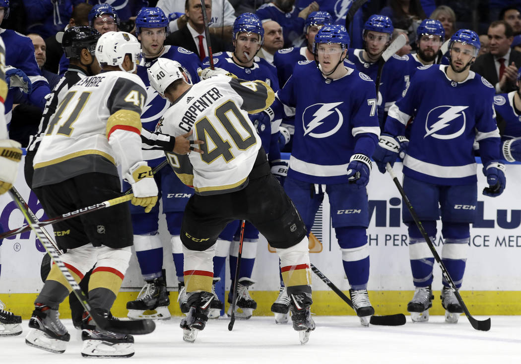 Vegas Golden Knights center Ryan Carpenter (40) loses his balance in front of the Tampa Bay Lightning bench after getting hurt on a check by center Cedric Paquette during the second period of an N ...