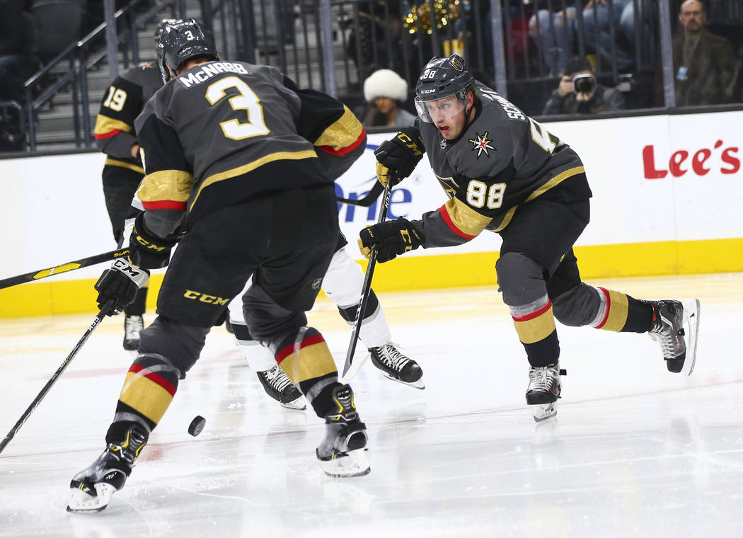 Golden Knights defenseman Nate Schmidt (88) sends the puck past defenseman Brayden McNabb (3) during the second period of an NHL hockey game against the Los Angeles Kings at T-Mobile Arena in Las ...