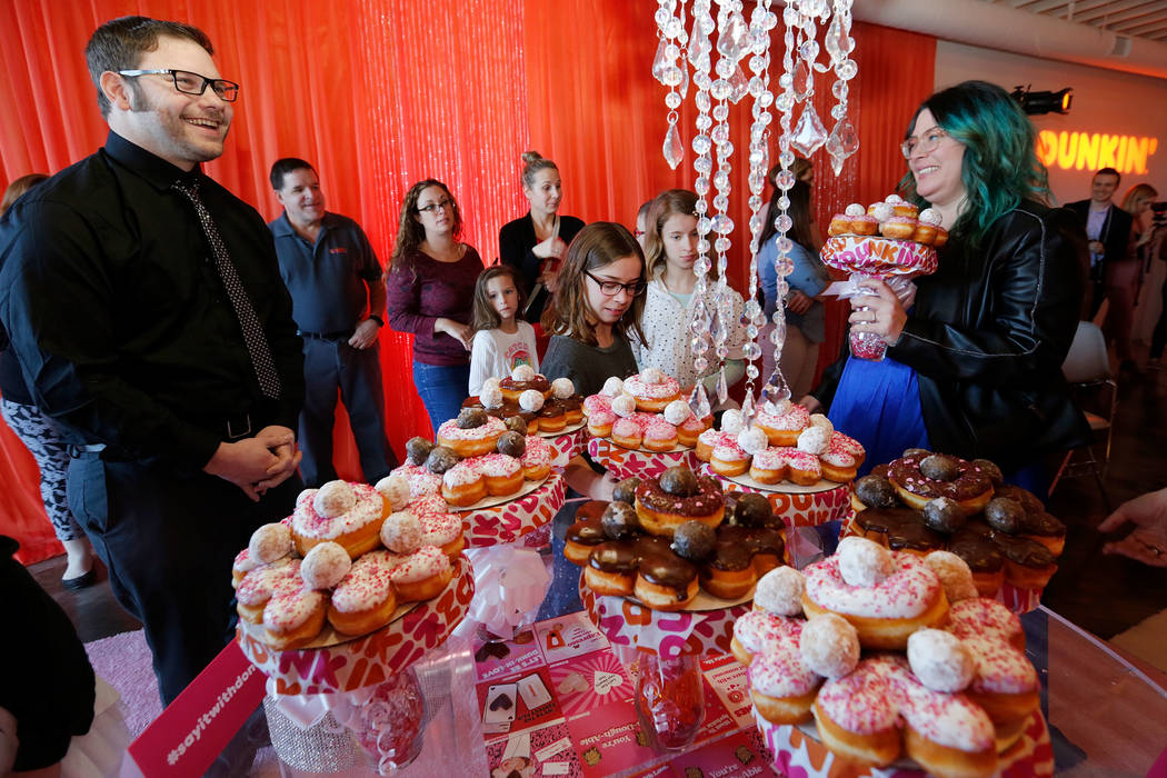 Jason Roberts of Las Vegas and his wife Erin smile after their vow renewal ceremony during a doughnut-themed wedding event in downtown Las Vegas, Saturday, Feb. 9, 2019. Dunkin' Donuts spreads som ...