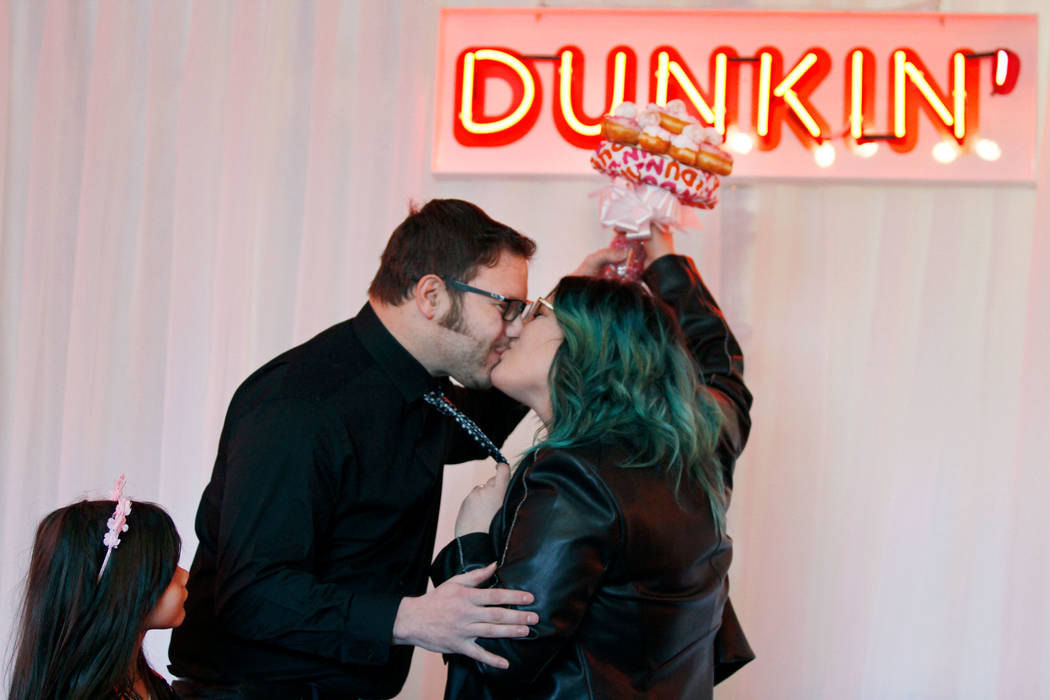 Jason Roberts of Las Vegas kisses his wife Erin during their vow renewal ceremony at a doughnut-themed wedding event in downtown Las Vegas, Saturday, Feb. 9, 2019, their daughter Layla, 5, looks o ...