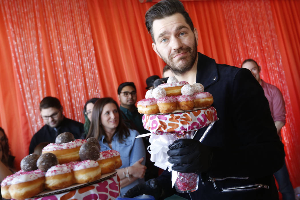 Pop artist Andy Grammer shows a donut bouquet he made during a doughnut-themed wedding event in downtown Las Vegas, Saturday, Feb. 9, 2019. Dunkin' Donuts spreads some love at Sure Thing Chapel to ...