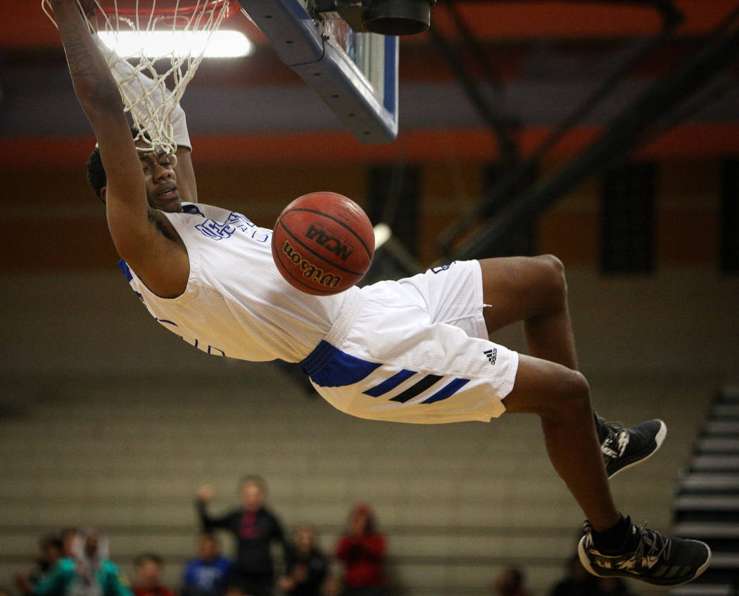 Desert Pines' Dayshawn Wiley (2) hangs from the net after dunking the ball during a basketball game against Canyon Springs High School at Desert Pines High School in Las Vegas, Tuesday, Feb. 5, 20 ...