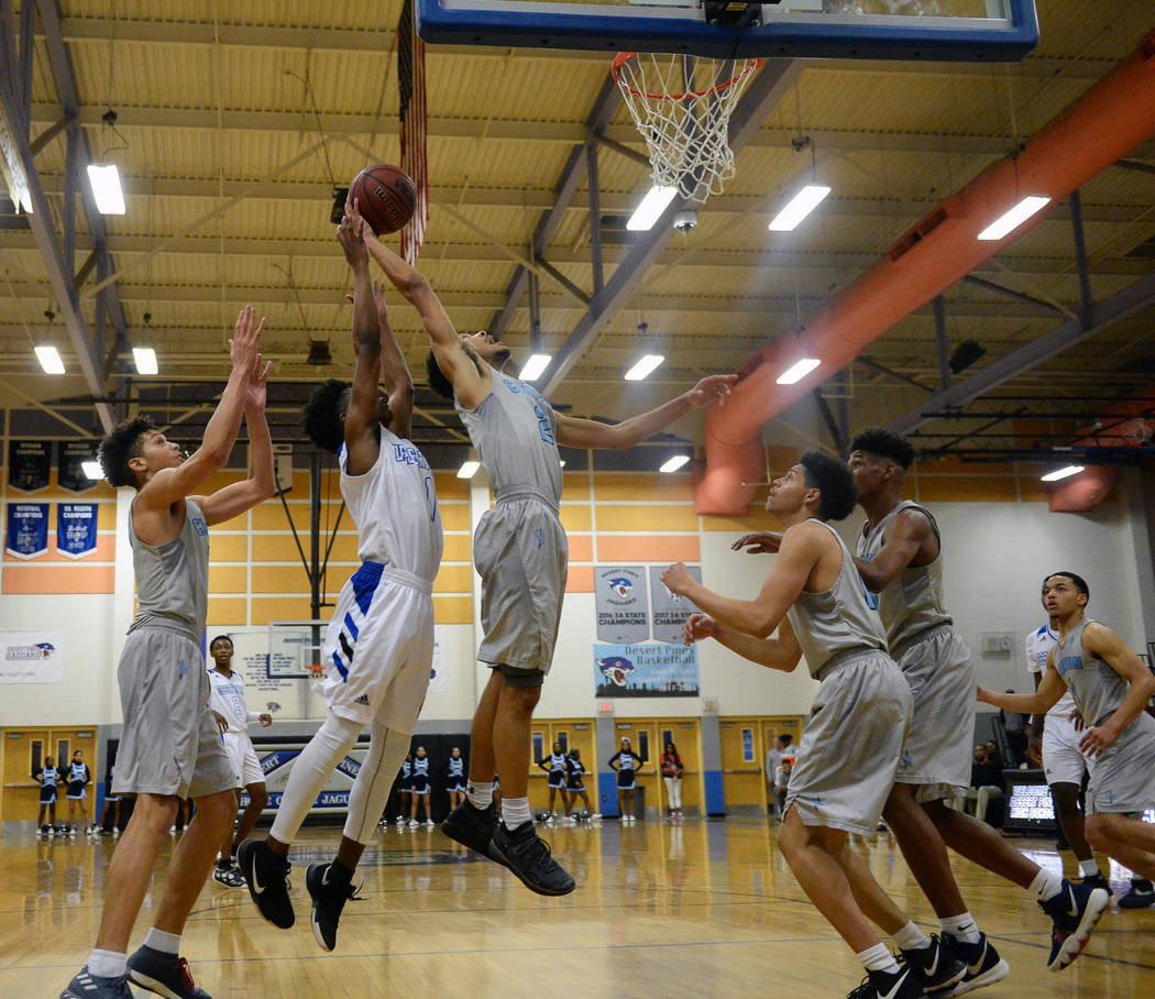 Canyon Springs' Alexander Spaight (2) jumps up to take a shot while under pressure from Desert Pines' Semaj Threats (1) during a basketball game at Desert Pines High School in Las Vegas, Tuesday, ...