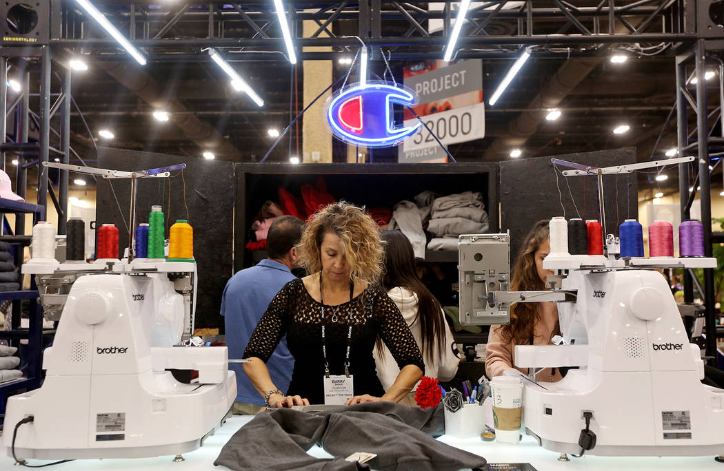 Maleatha Padilla prepares to embroider a sweatshirt at the Champion booth at the fashion trade show MAGIC at the Mandalay Bay Convention Center in Las Vegas, Tuesday, Feb. 5, 2019. (Rachel Aston/L ...