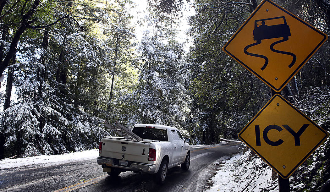 A truck drives past snow along the side of Alba Road above Ben Lomond in Bonny Doon, Calif., in Santa Cruz County, Tuesday, Feb. 5, 2019. Snow, ice and shivering cold blasted normally mild cities ...