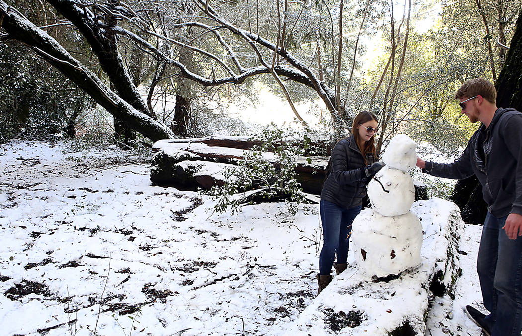 Sarah Fisher, left, and Patrick LaBarre play in the snow near the intersection of Empire Grade and Alba Road in Bonny Doon, Calif., in Santa Cruz County, Tuesday, Feb. 5, 2019. Snow, ice and shive ...