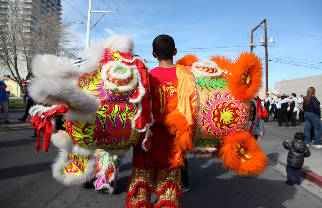Angel Alexis Angulo, 17, of Las Vegas holds the heads to a dragon before the beginning of the Chinese New Year parade on 4th Street in Las Vegas on Sunday, February 9, 2014. The parade is in its s ...