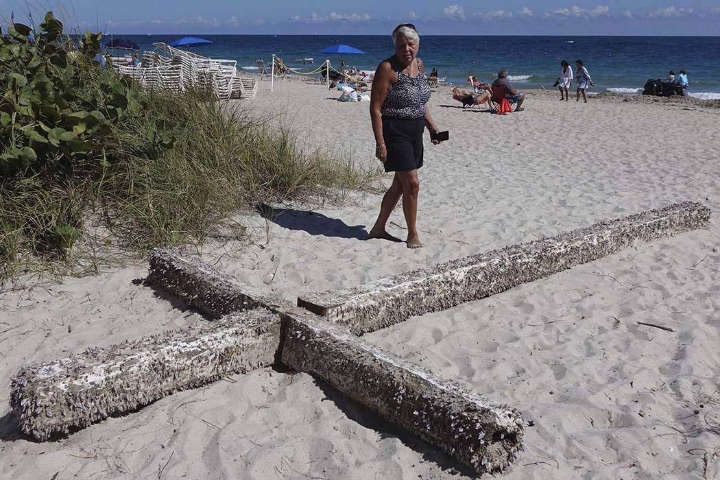 Aglair Rigos checks out the large, barnacle-covered wooden cross on the Galt Ocean Mile behind the Ocean Manor Beach Resort in Fort Lauderdale, Florida, on Tuesday, Feb. 5, 2019. (Joe Cavaretta/So ...
