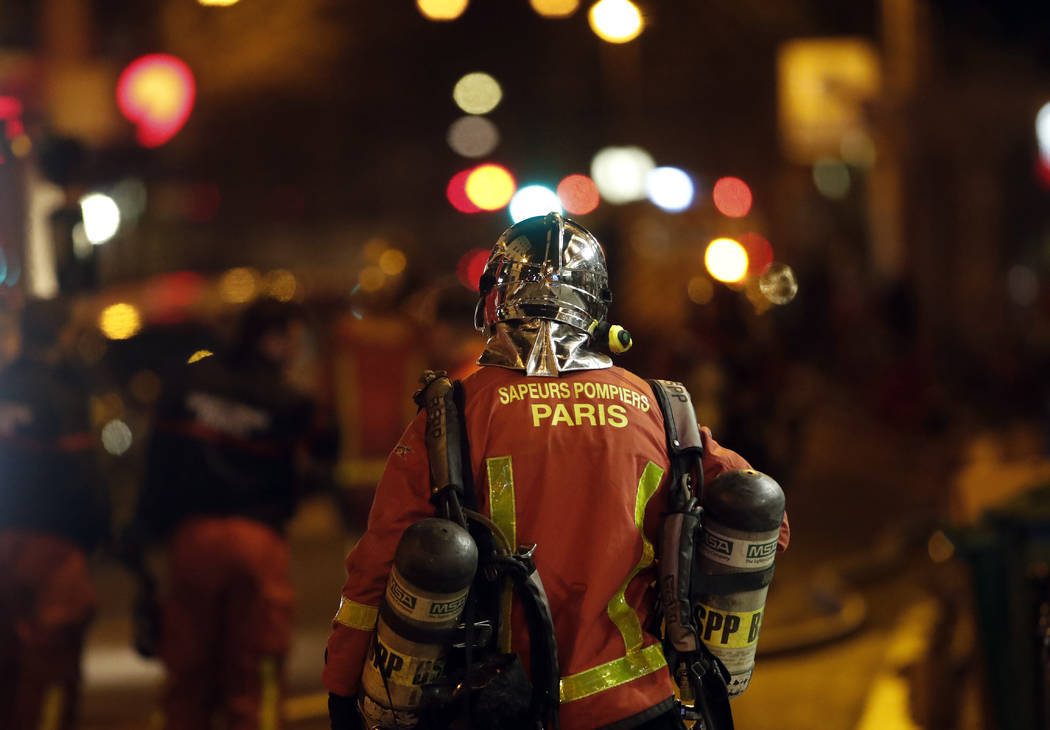 A Firefighter satnd on the scene of a fire in Paris, Tuesday, Feb. 5, 2019. A fire in a Paris apartment building early Tuesday killed seven people and sent residents fleeing to the roof or climbin ...
