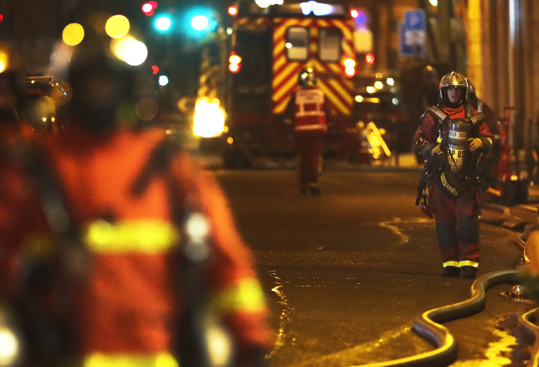 Firefighters stand on the scene of a fire in Paris, Tuesday, Feb. 5, 2019. A fire in a Paris apartment building early Tuesday killed seven people and sent residents fleeing to the roof or climbing ...