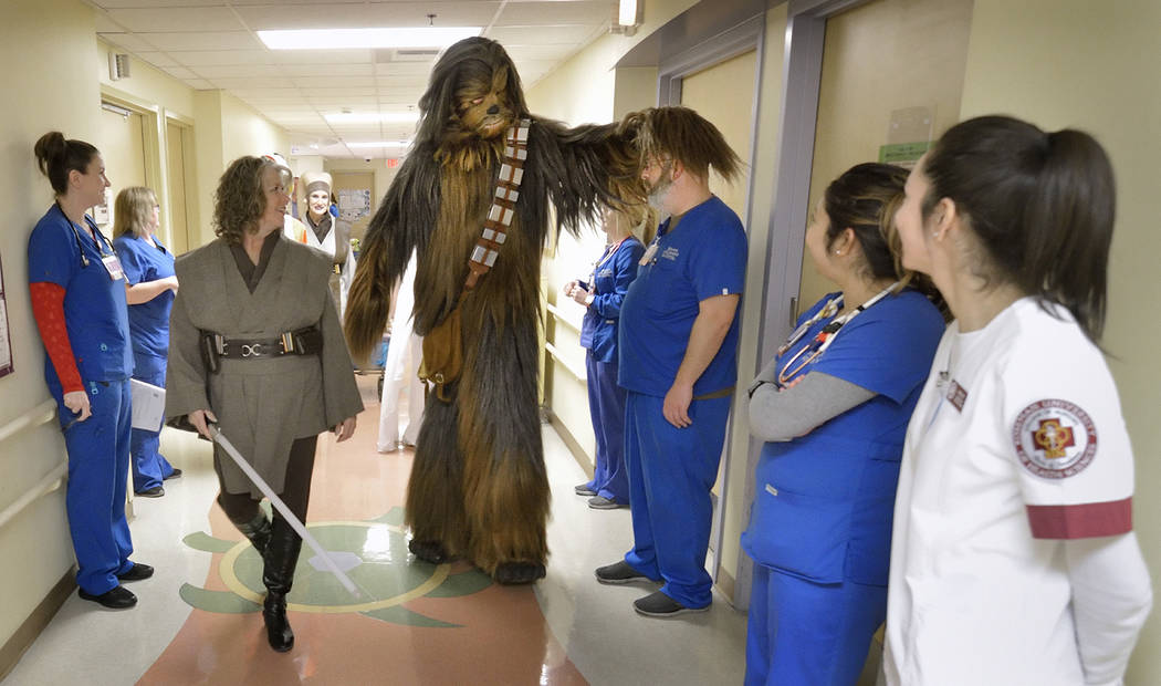 James Nocie, as Chewbacca, center, greets staff during a visit by members of the Rebel Legion Coruscant Base, a local chapter of an international Star Wars costuming organization, to Sunrise Child ...