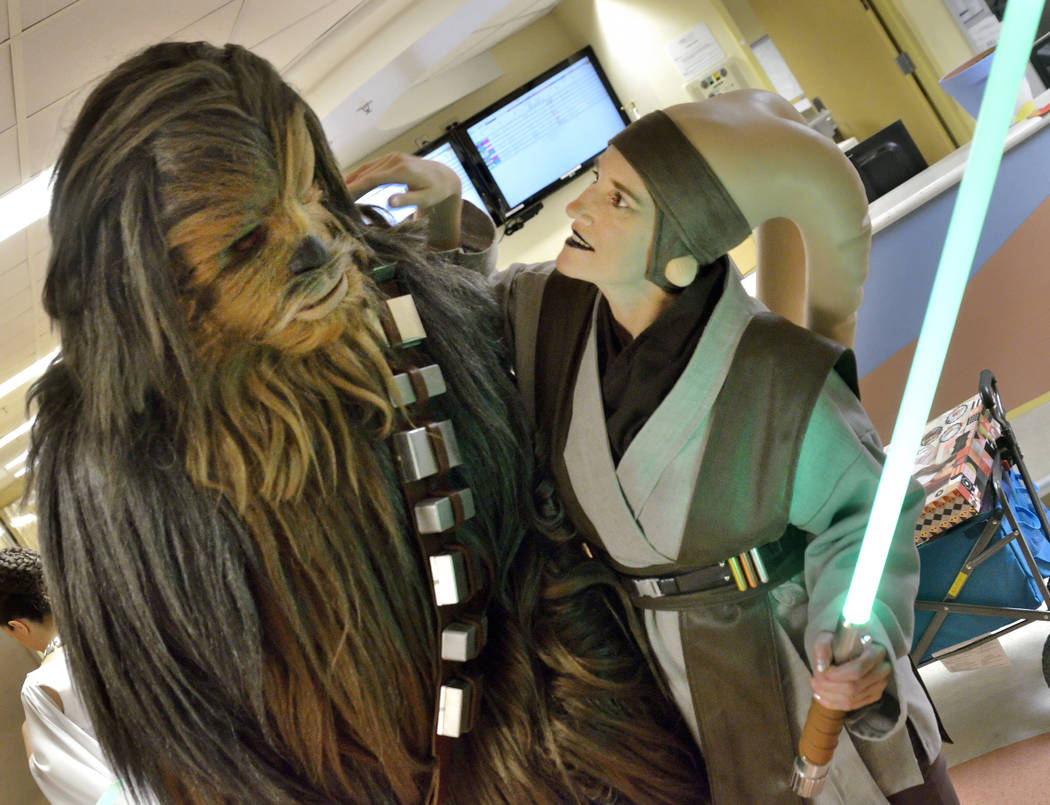 Mary Ann Nocie checks the costume of her husband James during a visit by members of the Rebel Legion Coruscant Base, a local chapter of an international Star Wars costuming organization, at Sunris ...