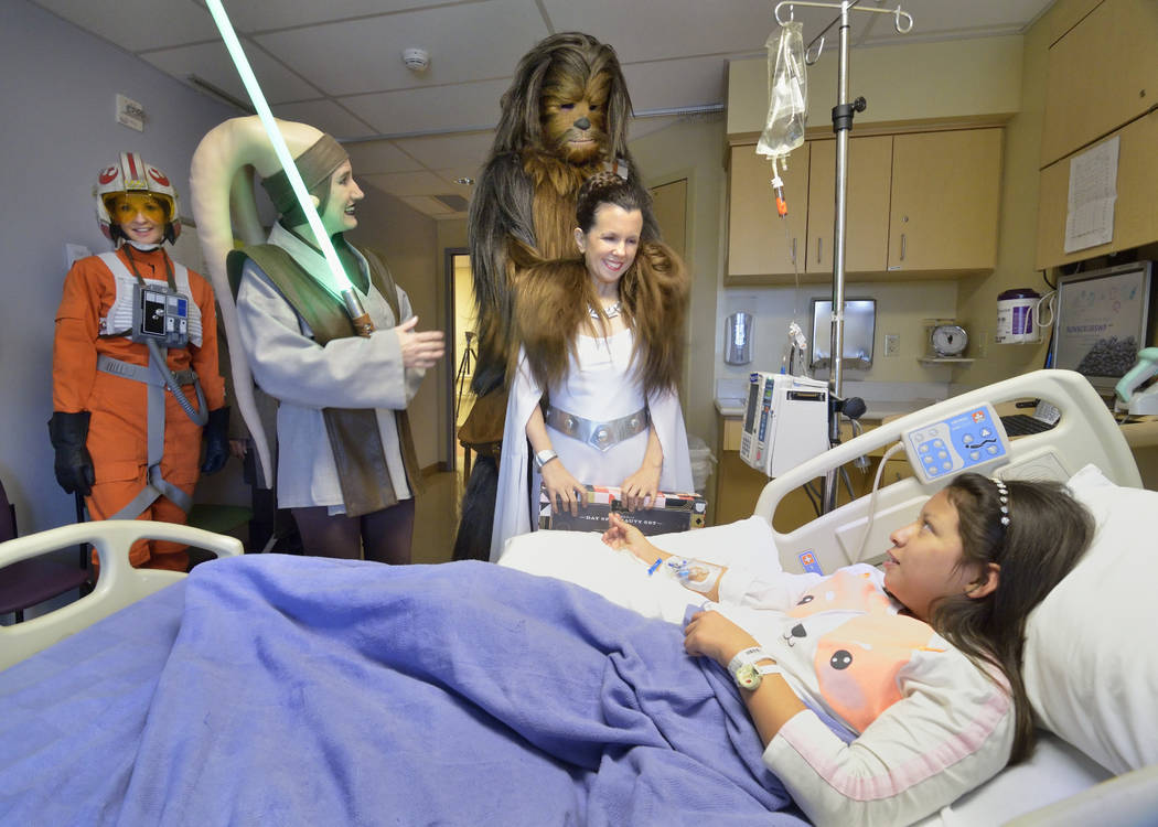 Kimberly Henriquez-Guevara, 11, is visited by members of the Rebel Legion Coruscant Base, a local chapter of an international Star Wars costuming organization, at Sunrise Children's Hospita ...