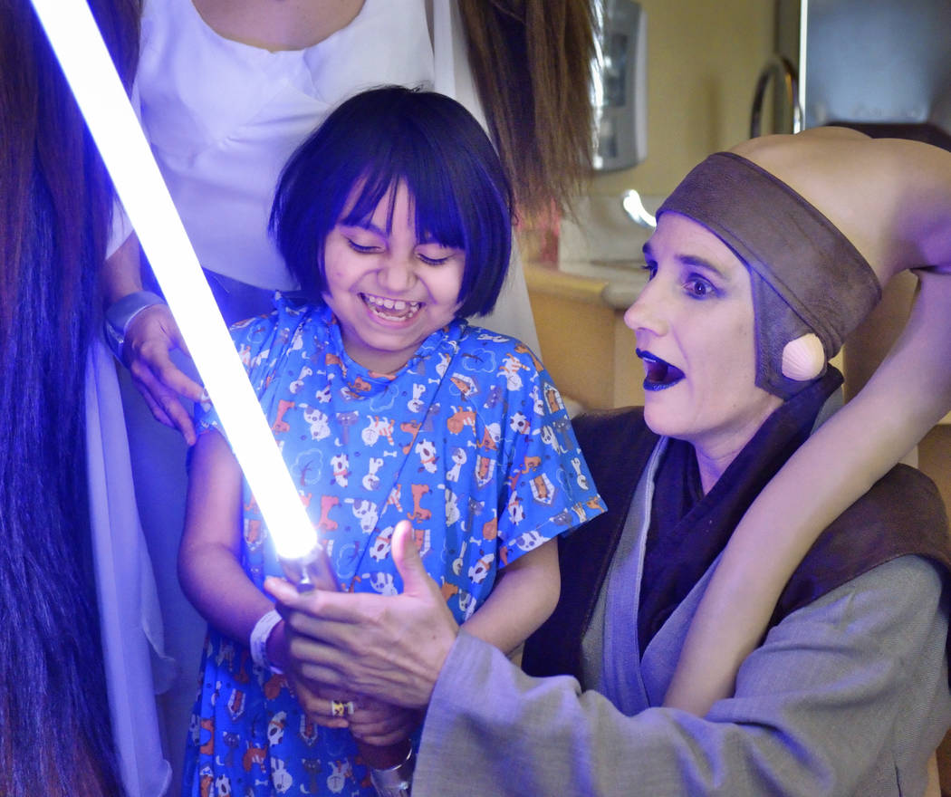 Abbie Jai Estrada, 10, gets a lesson on how to use a light saber from Mary Ann Nocie of the Rebel Legion Coruscant Base, a local chapter of an international Star Wars costuming organization, at Su ...