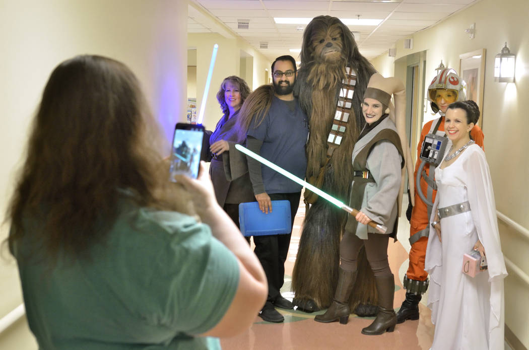 Krystle Hunter, child life specialist at Sunrise Children's Hospital, left, takes a picture of Nehaad Tahsin, a pharmacy technician with Walgreens, third from left, with members of the Rebel Legio ...