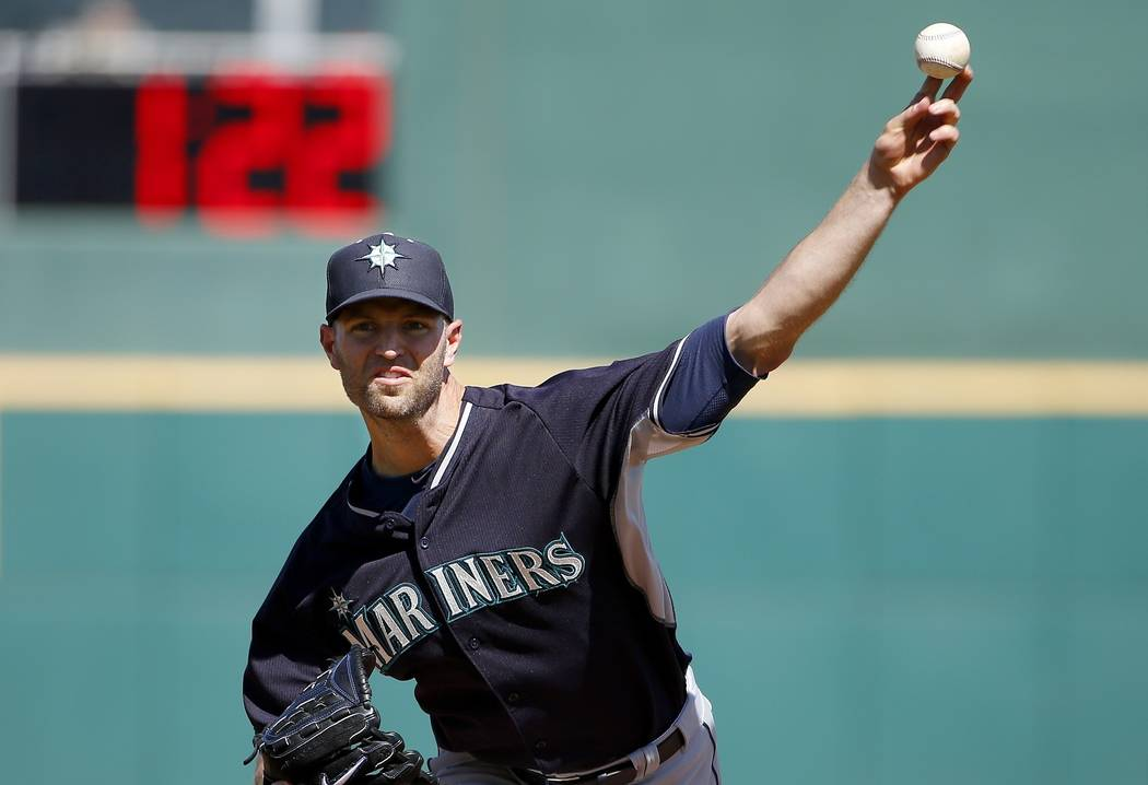 In this March 8, 2015, file photo, Seattle Mariners' J.A. Happ throws a pitch between innings as pitch clock counts down in the background during a spring training baseball game against the Cincin ...