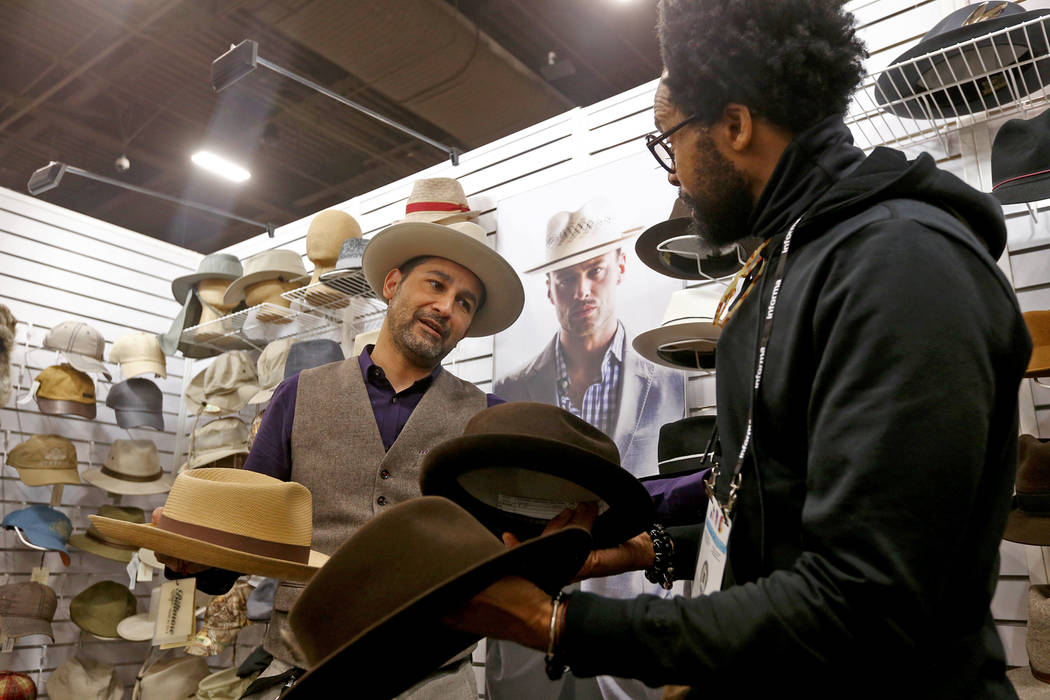 Victor Cornejo shows Kevin Scott different hats to purchase at the Biltmore Hats booth at the fashion trade show MAGIC at the Mandalay Bay Convention Center in Las Vegas, Wednesday, Feb. 6, 2019. ...