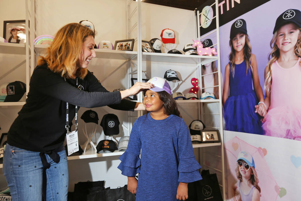 Director of sales Megan Klepacki places a trucker hat on Destiny Klatt, 9, at the Tiny Trucker Co. booth at the fashion trade show MAGIC at the Mandalay Bay Convention Center in Las Vegas, Wednesd ...