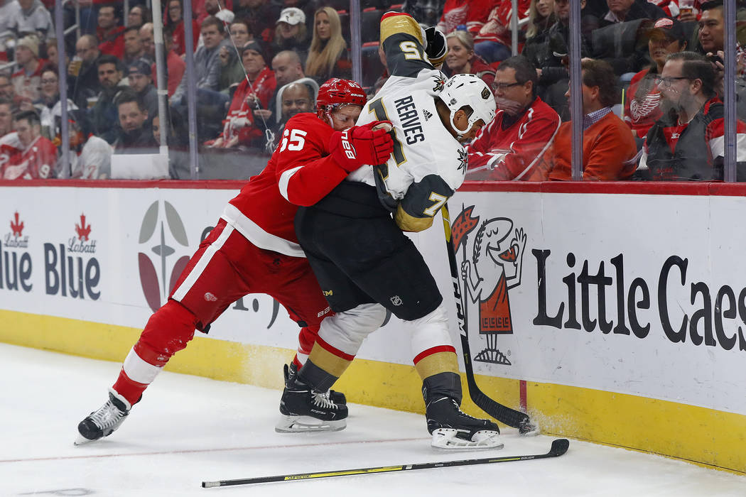 Detroit Red Wings defenseman Danny DeKeyser (65) battles with Vegas Golden Knights right wing Ryan Reaves (75) for the puck in the first period of an NHL hockey game Thursday, Feb. 7, 2019, in Det ...