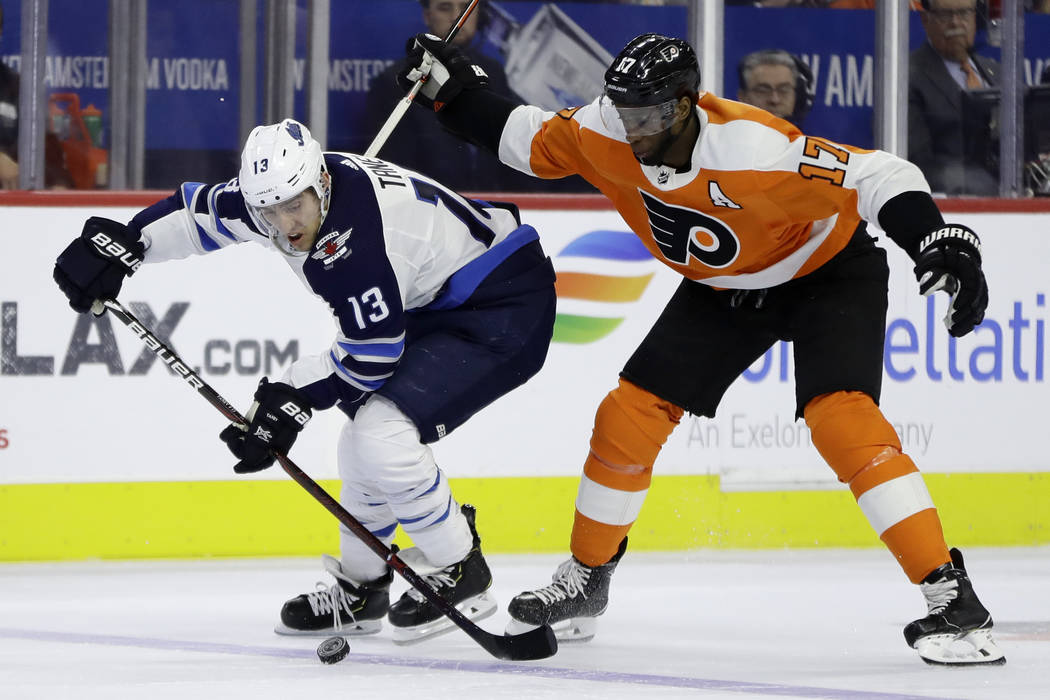 Winnipeg Jets' Brandon Tanev, left, and Philadelphia Flyers' Wayne Simmonds chase after the puck during the first period of an NHL hockey game, Monday, Jan. 28, 2019, in Philadelphia. (AP Photo/Ma ...