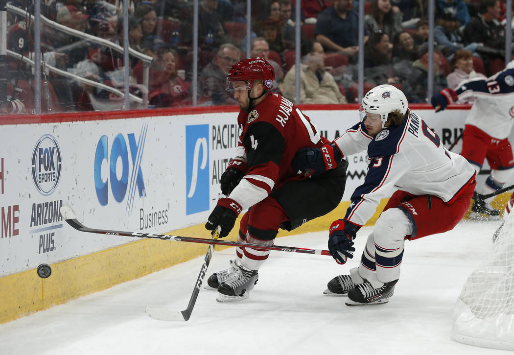 Arizona Coyotes defenseman Niklas Hjalmarsson (4) and Columbus Blue Jackets left wing Artemi Panarin (9) battle for the puck in the first period during an NHL hockey game, Thursday, Feb. 7, 2019, ...